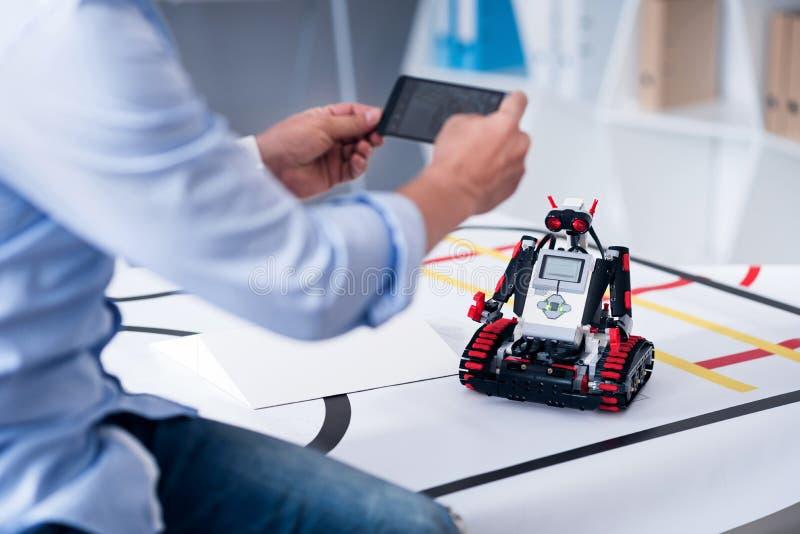 Varón que toma imágenes de un droid con el teléfono móvil fotografía de archivo libre de regalías