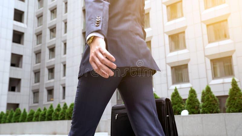 Varón seguro de sí mismo en traje de negocios que camina cerca de éxito constructivo de centro de la oficina imagen de archivo libre de regalías