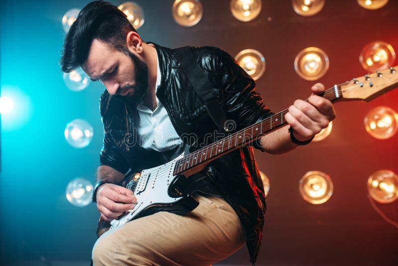 Varón a solas musican con la electro guitarra imagen de archivo