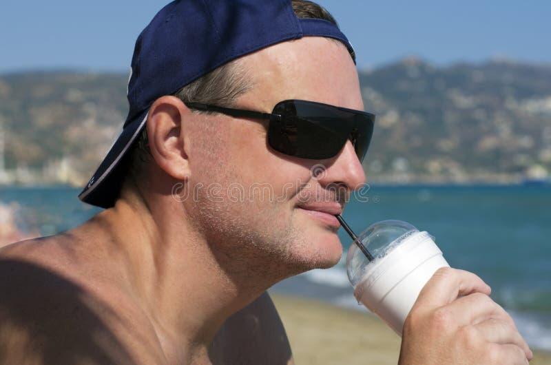 Varón sonriente en gafas de sol que bebe un cóctel foto de archivo