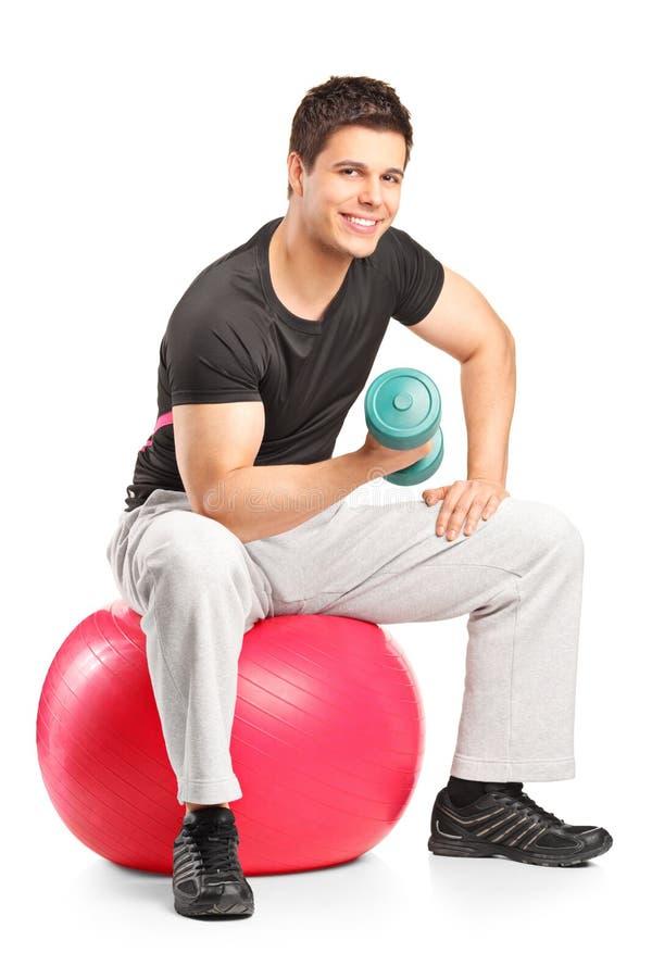 Varón sonriente que levanta encima de una pesa de gimnasia foto de archivo libre de regalías