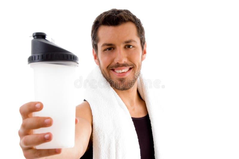 Varón sonriente que muestra la botella de agua foto de archivo