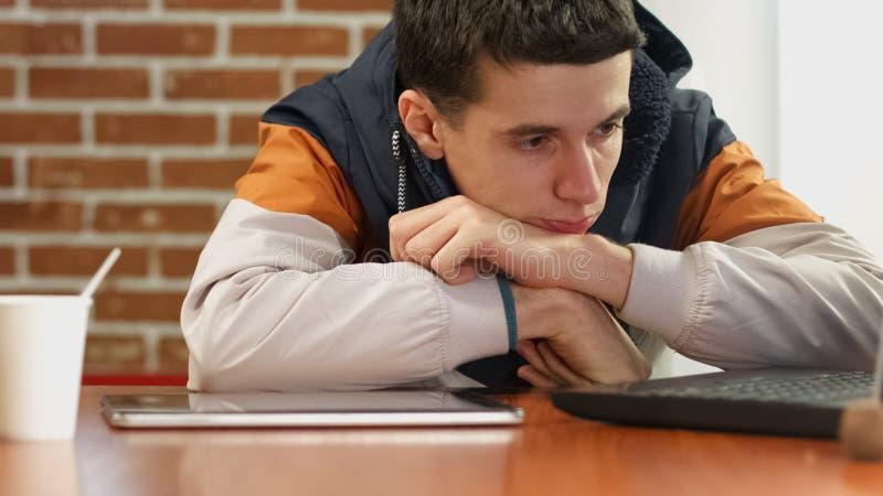 Varón triste joven que busca trabajo en línea usando el ordenador portátil, sensación agujereada, desempleo fotos de archivo