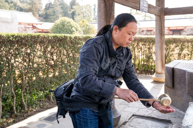 Varón turístico asiático que saca la capilla del agua con pala santa para lavarse las manos antes de entrar el templo de Todaiji, fotos de archivo