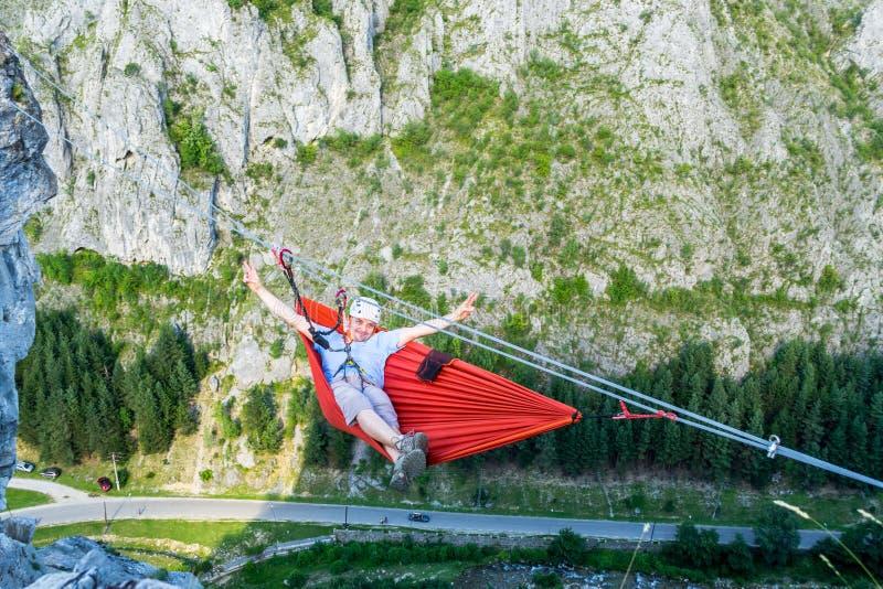Varón turístico relajado en un alto de la hamaca para arriba en una montaña, sobre el valle, asegurado con a vía sistema del ferr fotos de archivo
