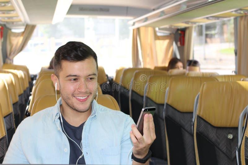 Varón usando su teléfono elegante durante un viaje agradable del autobús fotos de archivo