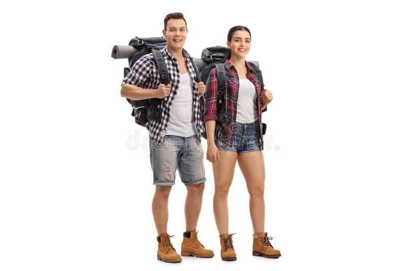 Varón y caminantes femeninos con las mochilas que colocan y que miran el th imagen de archivo