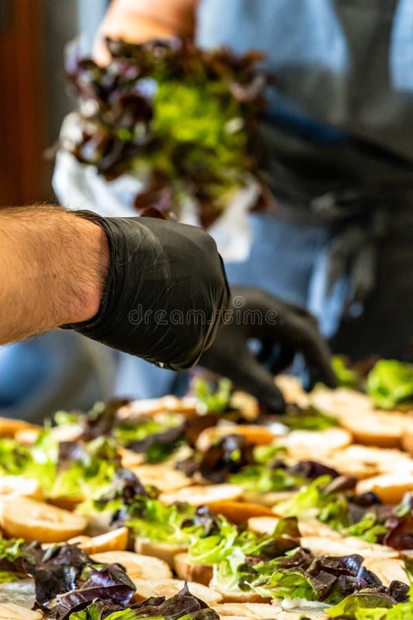 Varón y cocinero de sexo femenino Putting Ingredients de hamburguesas en una extensión cortada del pan en una tabla fotos de archivo libres de regalías