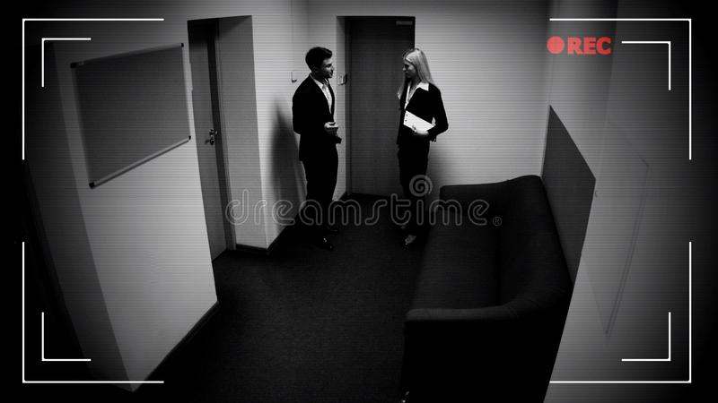 Varón y colegas femeninos que hablan el pasillo de la oficina, efecto de la cámara CCTV, cantidad foto de archivo libre de regalías