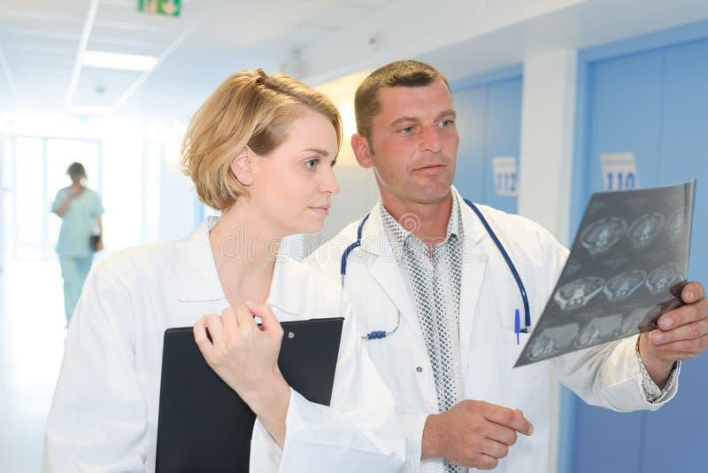 Varón y doctor de sexo femenino que comprueban la radiografía en el trabajo imagen de archivo