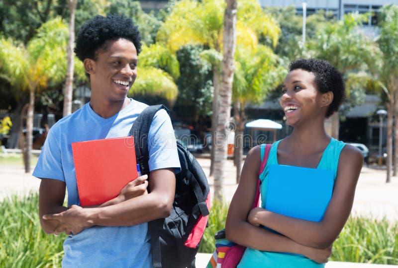 Varón y estudiante afroamericanos de risa en el campus de u foto de archivo libre de regalías