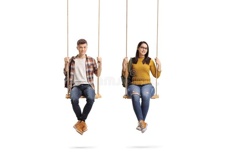Varón y estudiantes adolescentes femeninos que se sientan en un oscilación foto de archivo libre de regalías