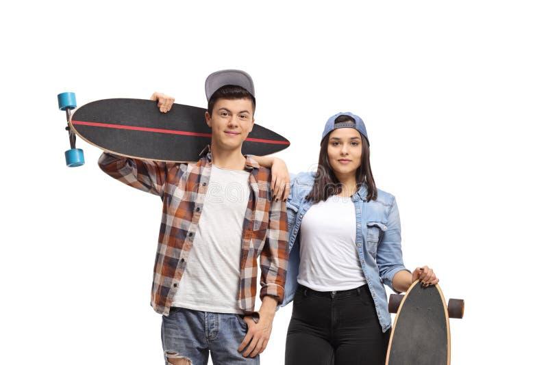 Varón y patinadores adolescentes de sexo femenino con longboards fotografía de archivo libre de regalías