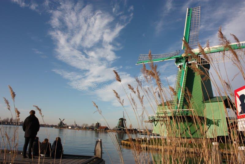 Var att g? och vad som ska g?ras i amsterdam en turist- by med en sikt av de typiska holland v?derkvarnarna som byggs av tr? arkivfoton
