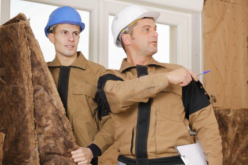 Var att sätta wood fiberisoleringsbräden på väggen royaltyfria foton