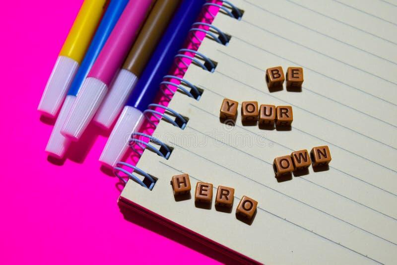 Var ditt eget hjältemeddelande som är skriftligt på träkvarter Motivationbegrepp Kors bearbetad bild arkivfoto