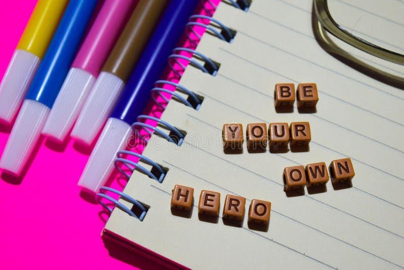 Var ditt eget hjältemeddelande som är skriftligt på träkvarter Motivationbegrepp Kors bearbetad bild royaltyfri foto