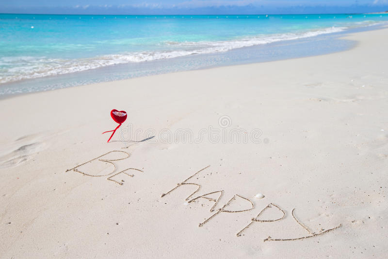 Var lycklig skriftlig i en sandig tropisk strand arkivbild