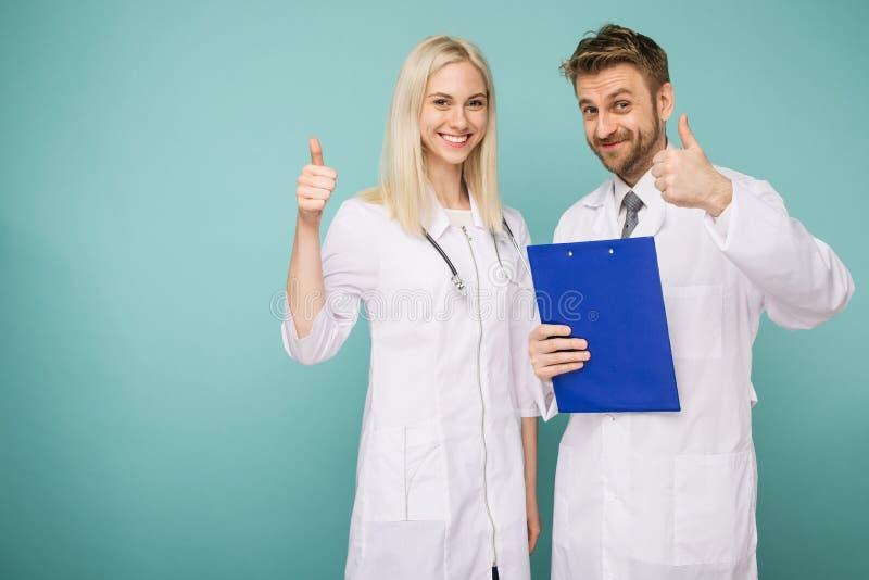 Var?n amistoso y doctores de sexo femenino Personas m?dicas felices de doctores Pulgar para arriba imagen de archivo libre de regalías