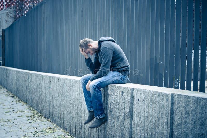 Var?n cauc?sico deprimido infeliz que se sienta en la sensaci?n urbana de la calle imagen de archivo