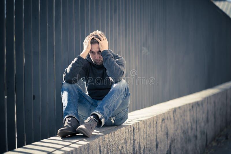 Var?n cauc?sico deprimido infeliz que se sienta en la sensaci?n urbana de la calle foto de archivo