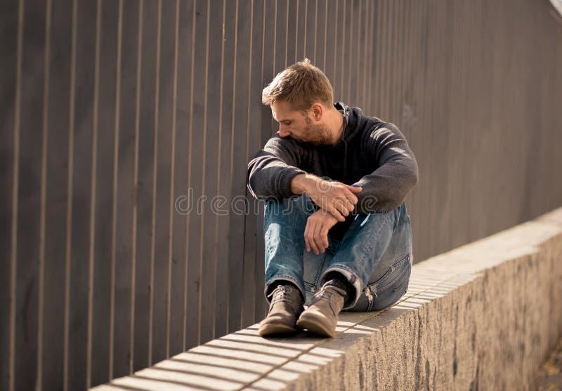 Var?n cauc?sico deprimido infeliz que se sienta en la sensaci?n urbana de la calle fotografía de archivo libre de regalías
