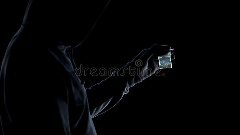 Var?n del drogadicto en la sudadera con capucha que mira el paquete con la anfetamina, problema del apego imágenes de archivo libres de regalías