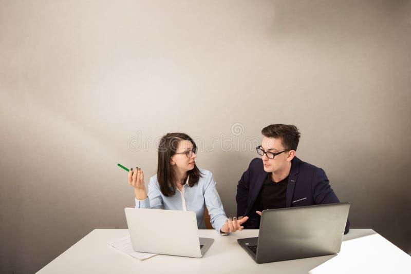 Var?n joven y socios comerciales femeninos que se sientan detr?s de un monitor de computadora y que piensan en algo imagen de archivo