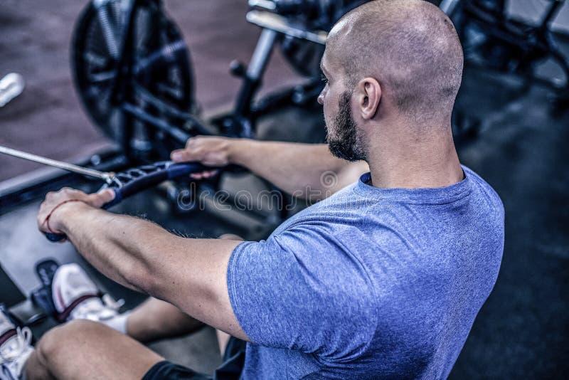 Var?n usando el aparato de remar en el club de fitness Hombre joven que hace ejercicios en la m?quina de la aptitud en gimnasio V fotos de archivo libres de regalías