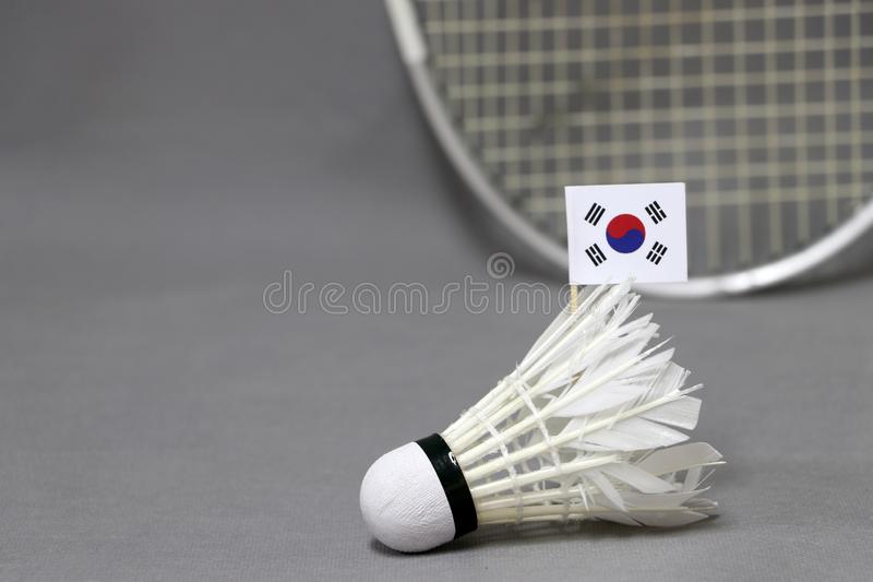 A vara da bandeira de Mini South Korea na peteca branca no fundo cinzento e focaliza para fora a raquete de badminton fotografia de stock