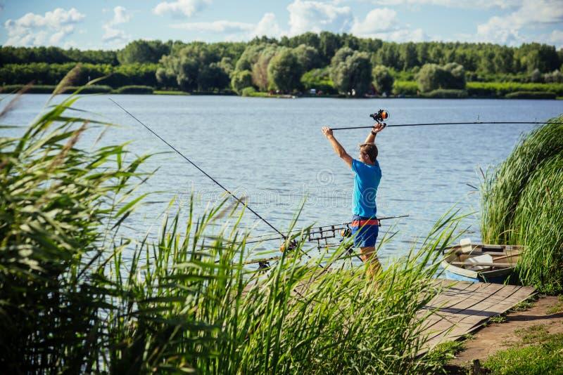 Vara de pesca do molde do pescador no lago ou na ?gua do rio imagem de stock royalty free