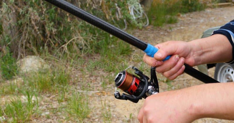 Vara de pesca do ` s do pescador com a bobina inércia-livre no verão na costa do fim do lago acima fotografia de stock