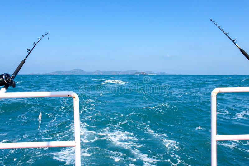 A vara de pesca e o calamar que penduram na linha de pesca são preparados à pesca a pouca distância do mar no barco no oceano imagens de stock