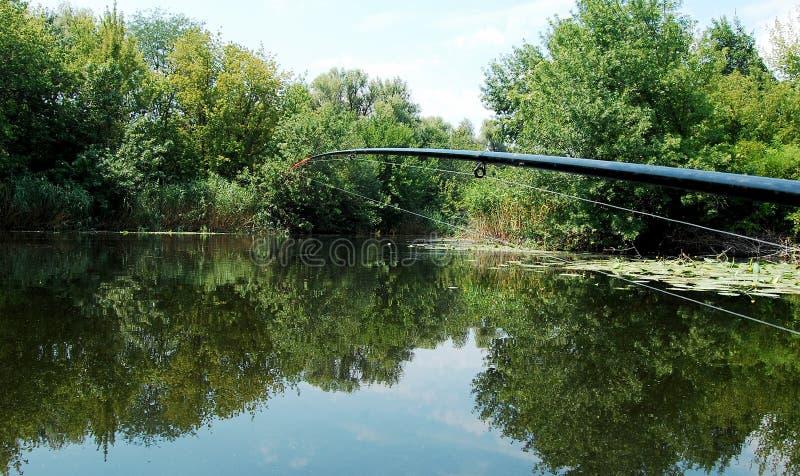 Vara de pesca no fundo da superfície lisa da água no meio-dia fotografia de stock
