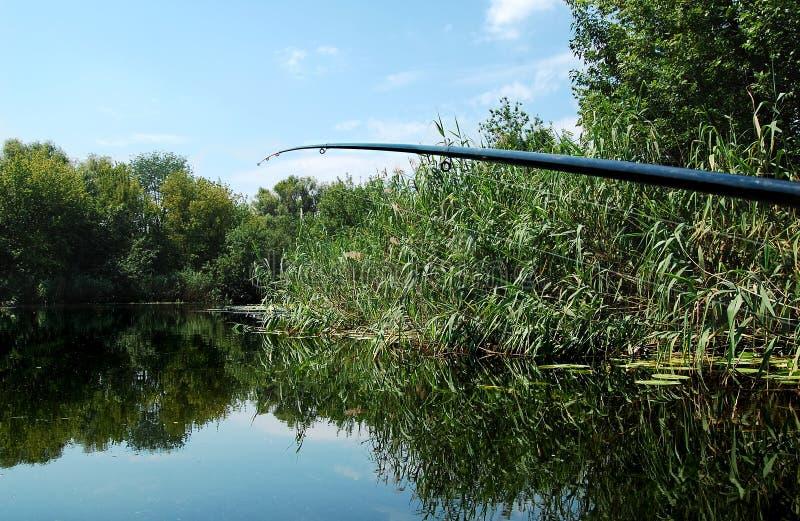 Vara de pesca no fundo da superfície lisa da água no meio-dia fotos de stock