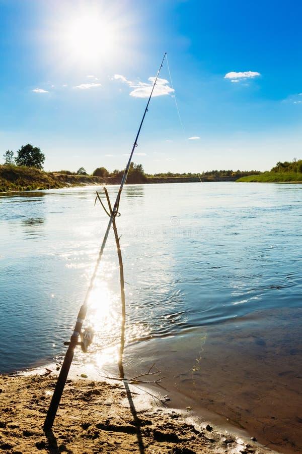 Vara de pesca só no banco de rio imagem de stock