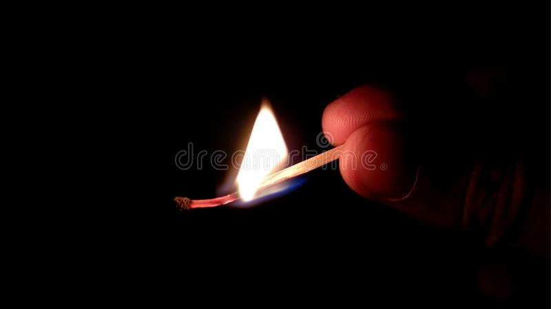 Vara do f?sforo que queima-se contra o fundo preto imagens de stock