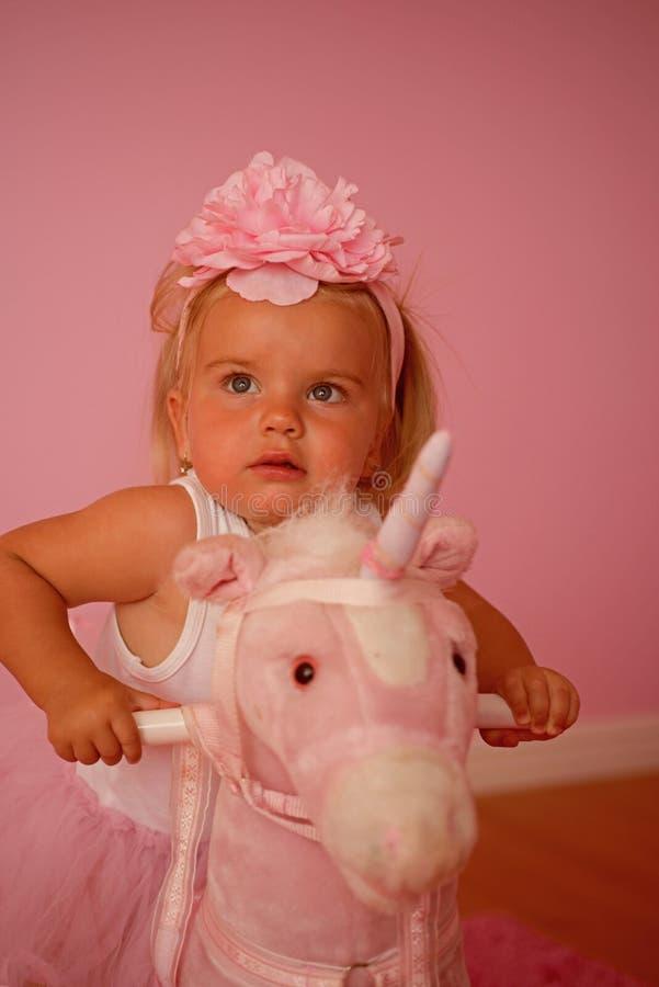 Vara i en sadel Musikband för småbarnkläderhår accessory hårhårnålwhite Liten blond häst för flickarittleksak Liten flicka med lä royaltyfria foton