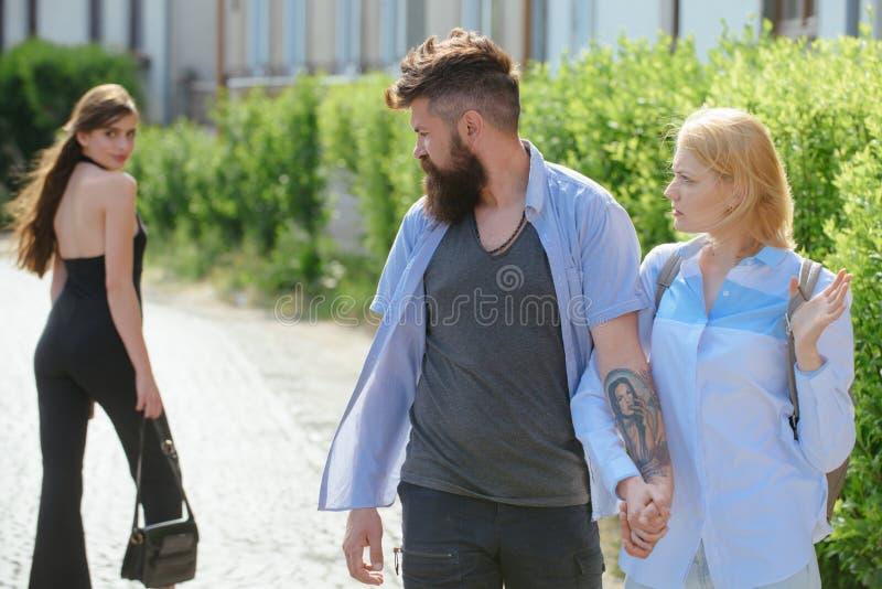Vara lite av en womaniser Hipster som väljer mellan två kvinnor Förälskelsetriangel och threesome Man som fuskar hans flickvän royaltyfri fotografi