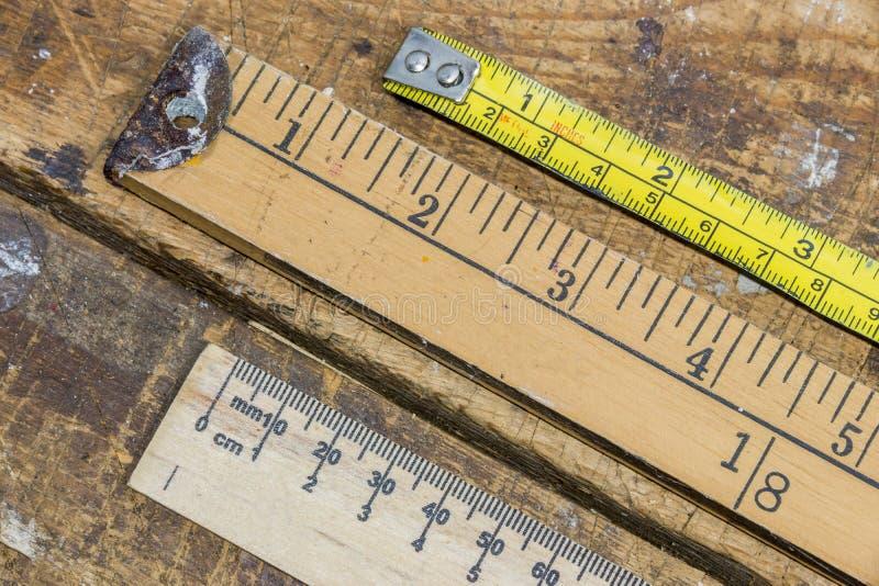Vara, régua e fita métrica velhas da jarda na aba riscada da oficina imagem de stock