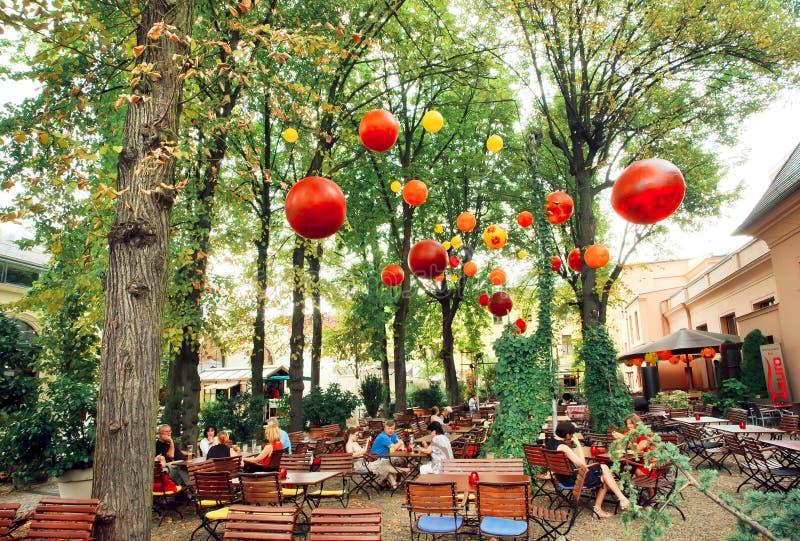 Vara slö restaurangen med folk som kopplar av under gröna träd royaltyfri fotografi