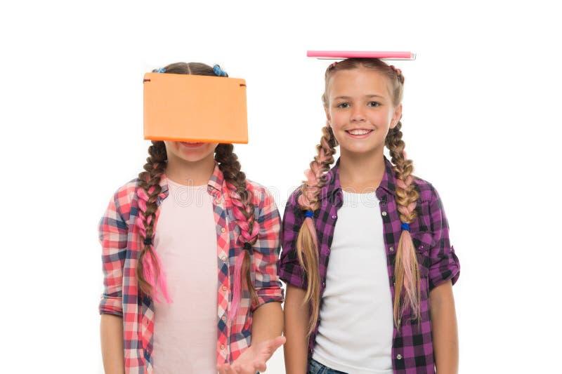 Vara snille för hård studie Snilleskolbarn som isoleras på vit Små flickor som rymmer böcker på huvud med snille royaltyfri foto