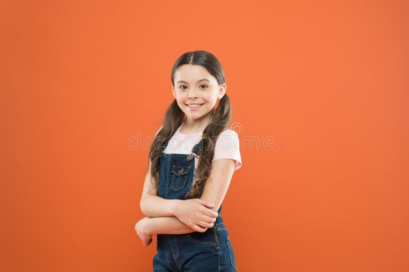 Vara utm?rkt varje dag behandla som ett barn modeflickan Gullig liten modemodell på orange bakgrund Sm?barn med modeblick arkivbild