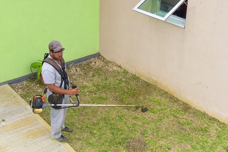 VARADERO, CUBA - JANUARY 05, 2018: A man shearing grass on a lawn in Varadero in Cuba royalty free stock image