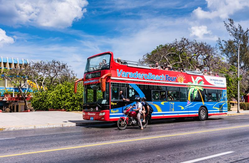 Varadero Beach Tour. Varadero, Cuba / March 19, 2016: Double decker tour bus and family on a motorbike cruising the Varadero beach town royalty free stock image