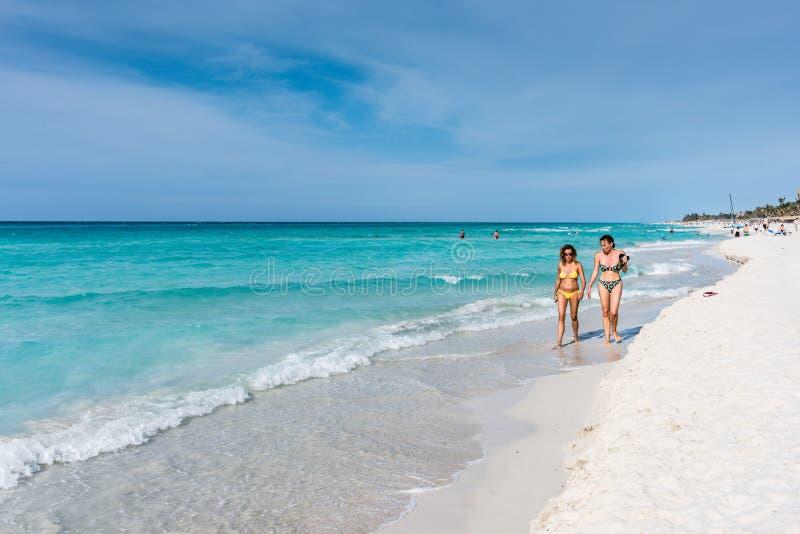 Women Walking on Varadero Beach. Varadero, Cuba / March 17, 2016: Two bikini clad women walking on the shore of Varadero Beach royalty free stock photos