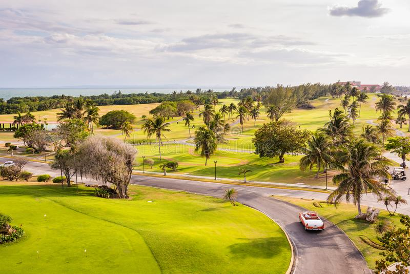Varadero Golf Club. Varadero, Cuba / March 19, 2016: Vintage convertible driving through Varadero Golf Club, the only 18 hole Golf Course in Cuba royalty free stock photography