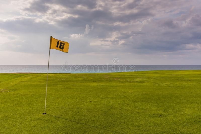 Eighteenth Hole - Varadero Golf Club. Varadero, Cuba / March 19, 2016: Yellow flag on smooth green lawn by the ocean at Cuban golf club royalty free stock photo