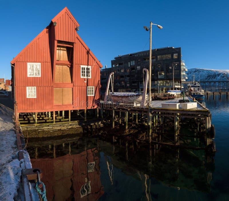 Varadero de madera rojo en los muelles del puerto de Tromsø en una mañana soleada fotografía de archivo