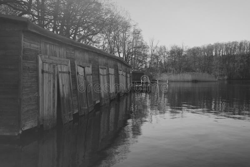 Varadero de madera viejo en el lago en la niebla de la madrugada, fotografía blanco y negro fotografía de archivo